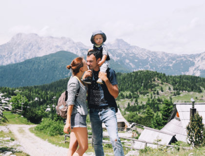 Beautiful happy family spends time on nature in the mountains. Family background. Lifestyle, Travel concept. Parent and child together. Velika Planina or Big Pasture Plateau in the Kamnik Alps, Slovenia